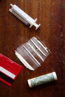 Lines of cocaine,syringe,credit card and dollar