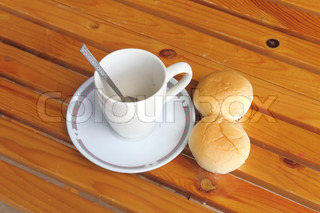 Bread with empty cup of coffee on the yellow wood table