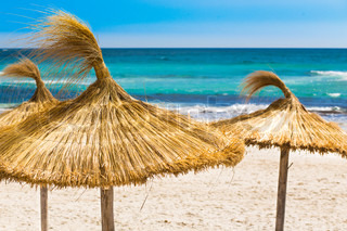 the sandy beach near the blue sea with straw umbrellas mallorca island spain stock photo. Black Bedroom Furniture Sets. Home Design Ideas