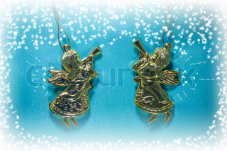 Two golden christmas angel playing trumpet on blue background
