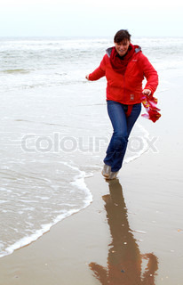 woman in red jacket touching a sand on cold beach