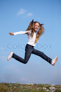 little girl happily jumping against the blue sky