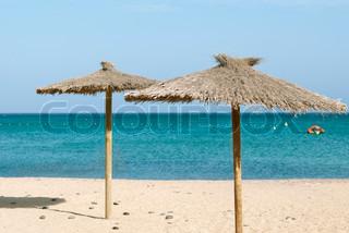 Thatch parasoller , sand, blå hav og himmel
