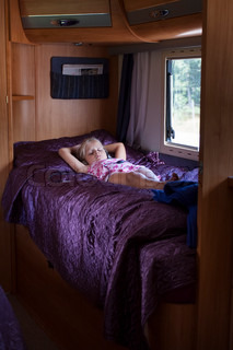 A Girl Sleeping In A Bunk Bed Inside A Moving Trailer