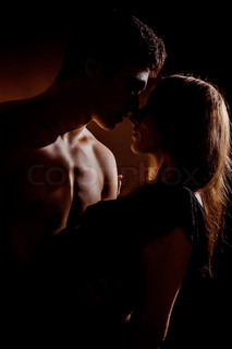 Beautiful young couple hugging and kissing isolated on black background