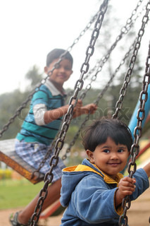 Cute young happy kids playing on swing sets in a park