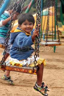 Beautiful &happy indian girlchild playing on a swing in a park