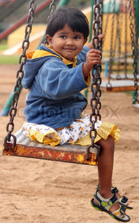 Cute young happy indian girlkid playing on a swing in a park