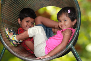Cute young childrenboy & girl playing in tunnel on playground