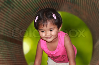 beautiful & cute young girl kid smiling & playing in a park