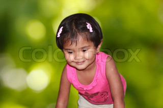 beautiful young girl child happily playing in a park