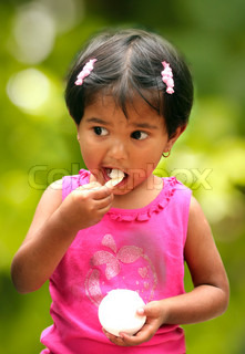 beautiful young indian girl child enjoying ice cream in a park