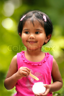 pretty young indian girl kid having fun eating ice cream in a park