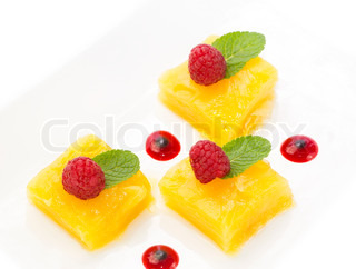 dessert of pineapple and decorated with raspberries on a white background