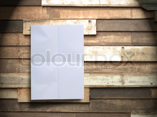 Wrinkled white paper on vintage wood wall panel with spotlight