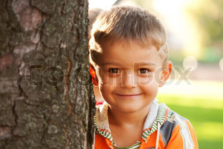 Handsome smiling little boy near a tree