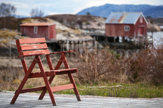 Red wooden chair in small Norwegianvillage on the sea coast