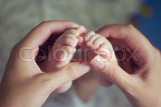 Little baby feet with mother hand