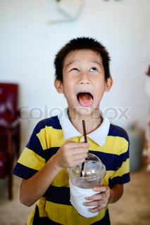 Asian boy with funny face drinking chocolate