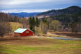 Springtime, empty rural Norwegian landscape with red wooden houses and forest on hills