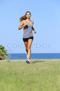 Front view of a beautiful woman running on the grass