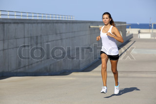 Attractive woman running on the asphalt
