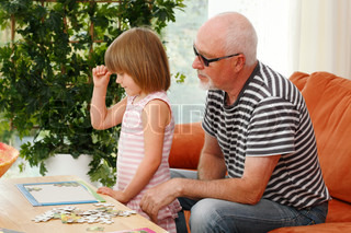 hesitant little girl doing a puzzle while grandpa is watching
