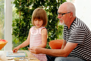grandpa helping little girl doing a puzzle indoors at table