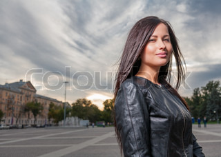 russian brunette 20s years old posing outdoors weared black leather jacket
