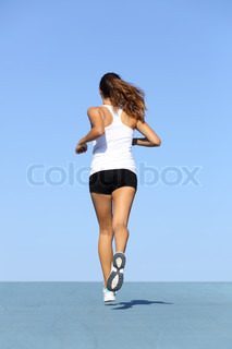 Back view of a fitness woman running on blue
