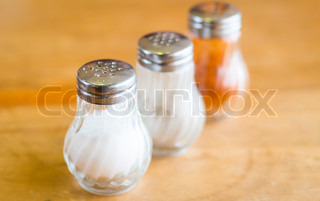 salt and pepper in shaker glass bottle on wood table