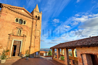 Red brick catholic church on small cobbled square under beautiful blue sky with white clouds in town of Monticello D'Alba in Piedmont, Italy.