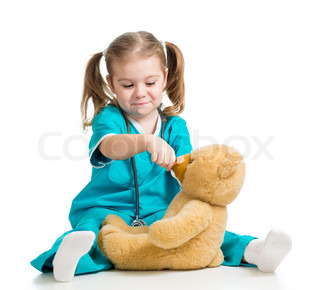 Adorable girl with clothes of doctor spoon feeding teddy bear over white