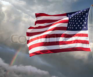 American flag against a cloudy sky with a rainbow