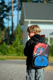 profile of little boy walking to schoold with big bag on his back