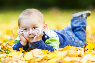 little boy lying on the yellow leaves in the autumn park