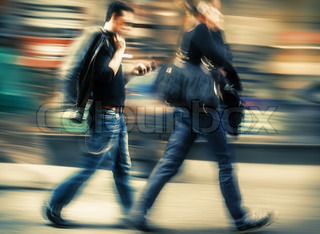 Man and woman talking on a cell phone in a hurry