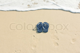 Sandals on beach and sea wave