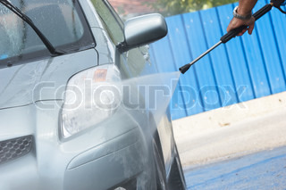 Water spray gun, held by a man, used to wash a car