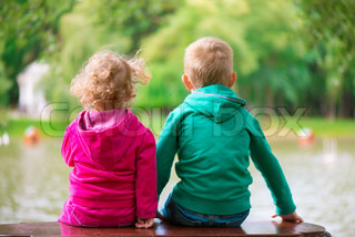 Little sister and brother sitting on bench at pond