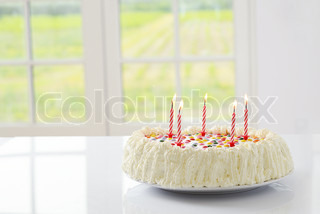 Birthday cake with colourful sprinkles and lit candles