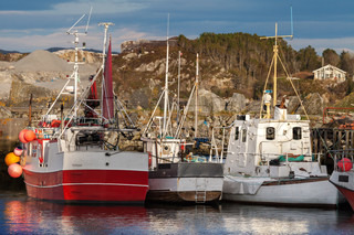 Red and white small fishing boats moored in small Norwegian village
