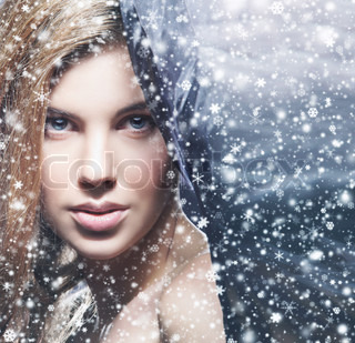 Beauty portrait of young attractive woman over snowy Christmas background