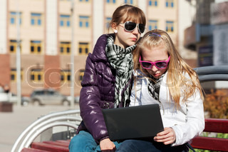 Teenage schoolgirls using laptop on the bench
