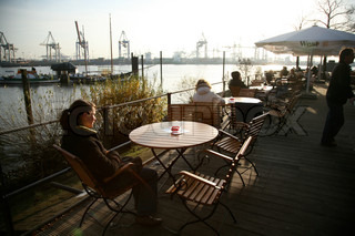 People sitting in outdoor cafe on harbour in Hamburg