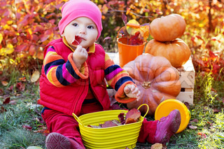 Cute baby girl with pumpkins in autumn garden