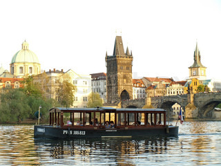 Charles Bridge of Prague with a boat on river Vltava