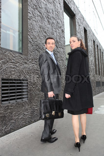 businessman and businesswoman walking in the street