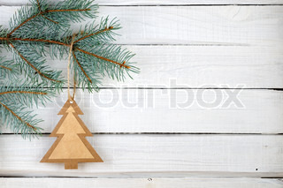 Paper Christmas tree and branches of blue spruce on wooden background