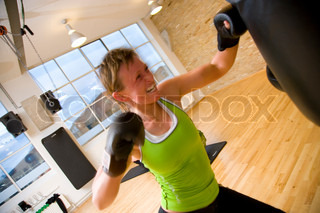A caucasian woman boxing in a fitness center